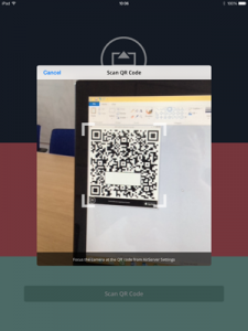 The camera on the iPad is now pointing at a computer screen showing a QR code