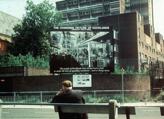 Docklands Community Poster Project, Loraine Leeson and Peter Dunn. The poster reads: 'The Changing Picture of Docklands: The people of Docklands have always had to fight to make the best of appalling conditions – and to change them'.  Photo-mural on hoarding, Wapping. (Image Source: )
