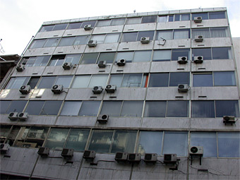 photo of haphazard installation of split aircon units in a tower block